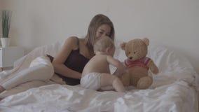 Kleines Baby, das zu Hause auf dem Bett spielt Nette Mutter, die nahe Kind sitzt Reizendes Kind, das auf dem Bett climbling ist K stock footage