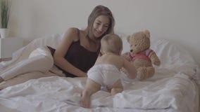 Kleines Baby, das zu Hause auf dem Bett spielt Nette Mutter, die nahe Kind sitzt Reizendes Kind, das auf dem Bett climbling ist K stock video footage