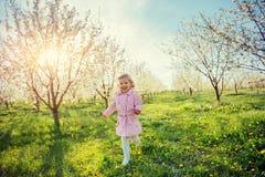 Kleines Baby, das zwischen blühende Bäume bei Sonnenuntergang läuft AR Lizenzfreies Stockfoto