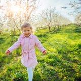 Kleines Baby, das zwischen blühende Bäume bei Sonnenuntergang läuft AR Stockfotos