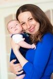 Kleines Baby in den Armen der Mutter Stockbilder