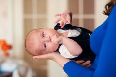 Kleines Baby in den Armen der Mutter Stockbild