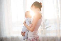 Kleines Baby in den Armen ihres Mutterwohnzimmers Stockbild