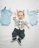 Kleines Baby in den Jeans, die an der Schnur nahe bei trocknender Kleidung hängen Stockbild