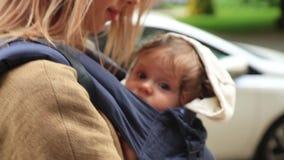 Kleines Baby in der Fördermaschine mit Mutter an im Freien stock video