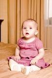 Kleines Baby des Lächelns im roten Kleid, das auf dem Boden sitzt Stockbilder