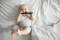 Kleines Baby hält einen Smartphone und hört Musik beim Lügen auf einem hellen Bett lizenzfreies stockfoto