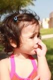 Kleines Baby, ihren Daumen im Park saugend Stockfotos