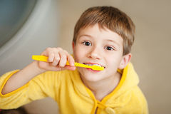 Kleines Baby im gelben Bademantel mit Zahnbürste stockfoto