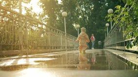 Kleines Baby im orange wasserdichten Regenmantel und in den Gummiregenstiefelwegen auf Pfützen zu ihrer Mutter, Zeitlupeschuß