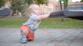 Kleines Baby lernt, entlang die Bank zu gehen Im Park outdoor stock footage