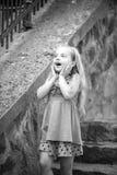Kleines Baby mit überraschtem Gesicht im blauen Kleid im Freien Stockfotos