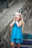 Kleines Baby mit überraschtem Gesicht im blauen Kleid im Freien Lizenzfreie Stockfotografie