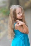 Kleines Baby mit dem langen Haar im blauen Kleid im Freien Lizenzfreie Stockfotos