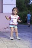 Kleines Baby mit den Zöpfen, die das Endhandzeichen machen Lizenzfreies Stockbild