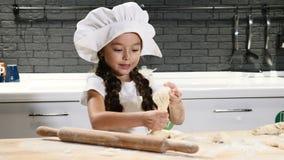 kleines Baby mit einem großen Löffel Kleines Mädchen im Chefhut, der mit Teig und Nudelholz spielt Lachen, Spaß in der Küche habe stock footage