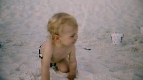 Kleines Baby mit einem Spielzeug, das am Strand kriecht Lizenzfreie Stockfotos