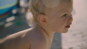 Kleines Baby mit einem Spielzeug, das am Strand kriecht stock footage