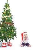 Kleines Baby mit einem Weihnachtsbaum und einem Ball Lizenzfreie Stockfotos