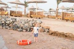 Kleines Baby mit entzückendem Gesicht mit Rettungsgürtel auf Strand Stockbild