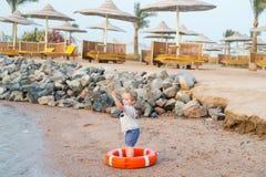 Kleines Baby mit entzückendem Gesicht mit Rettungsgürtel auf Strand Lizenzfreie Stockfotos