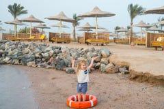 Kleines Baby mit glücklichem Gesicht mit Rettungsgürtel auf Strand Stockfotografie
