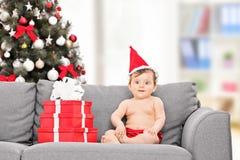 Kleines Baby mit Sankt-Hut, der auf Couch sitzt Stockfotografie