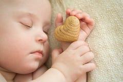 Kleines Baby schläft mit einem hölzernen Herzen in der Hand Lizenzfreie Stockfotos