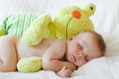 Kleines Baby, schlafend mit großem Teddybärfrosch Stockfotografie