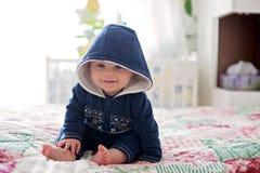 Kleines Baby, sitzend im Bett und lächeln Lizenzfreie Stockbilder