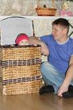 Kleines Baby sitzt in der großen Flechtweide und Vater betrachtet sie Lizenzfreie Stockfotografie