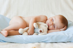 Kleines Baby und sein Teddybärspielzeug lizenzfreies stockbild