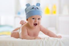 Kleines Baby weared im lustigen Hut, der sich auf einer Decke hinlegt Stockbild