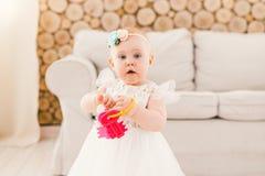 Kleines Baby in weißem verschwenden das Kleid, das im Wohnzimmer im Haus auf Sofa und hölzernem Wandhintergrund steht und a hält Lizenzfreies Stockfoto
