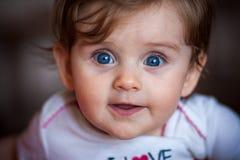 Kleines Baby, welches die Kamera mit einem Lächeln betrachtet stockfoto