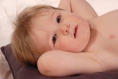 Kleines Baby wirft für die Kamera auf, die auf Kissen legt Lizenzfreie Stockbilder