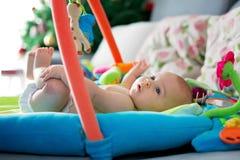 Kleines Baby, zu Hause spielend mit bunten Spielwaren stockbilder