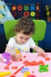 Kleines Babykind, das auf dem Tisch Plasticine spielt Lizenzfreie Stockbilder