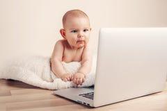 Kleines Babykind, das das Lernen auf dem drahtlosen ernsten Gesicht des Laptops spielend arbeitet Lizenzfreie Stockfotos