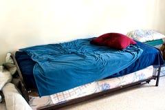 Kleines benutztes Bett im weißen Raum Stockbild