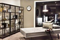Kleines Bett und Kissen neben einem Regal mit fantastischen Einzelteilen Stockfotos