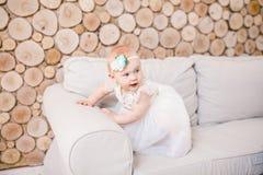 Kleines blauäugiges Mädchen blond in einem weißen Tüllkleid mit einer Dekoration auf ihrem Kopf, der auf einem beige Sofa in eine Lizenzfreies Stockfoto
