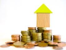 Kleines Blockhaus, das auf einem Stapel von Münzen steht Stockbilder