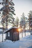Kleines Blockhaus hinter Aufdampfungsfluß im Winter herein Stockfotografie