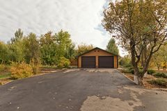 Kleines Blockhaus mit der Garage mit 2 Autos errichtet weg von Stadt im Wald Stockbild