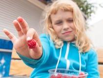 Kleines blondes aktives Mädchen hielt heraus frische Himbeere an Lizenzfreie Stockfotos