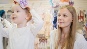 Kleines blondes Baby mit der Mutter, die Einkaufs- und Kaufenhut in den Kindern tut, kleiden Speicher Lizenzfreie Stockfotos