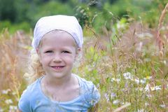 Kleines blondes behaartes gelocktes Mädchen in einem Dorf Stockfotografie