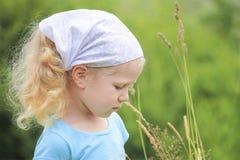 Kleines blondes behaartes gelocktes Mädchen in einem Dorf Lizenzfreie Stockbilder