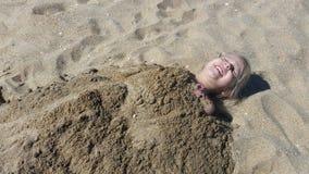 Kleines blondes behaartes Mädchen, das im Sand begraben erhält Stockbilder